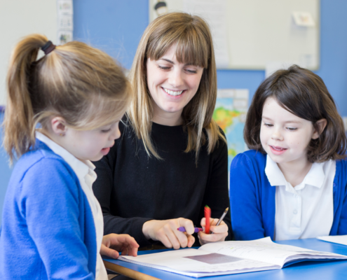 A teacher explains a mathematical sum to two pupils at The Meadows Primary School